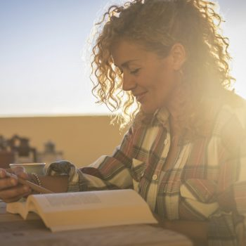 Beautiful happy smiling relaxing caucasian curly blonde woman reading a book dunring the sunlight sunset on the terrace outdoor at home - hipster female people studying and learning